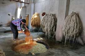 Pour the vegetal pigments in pot in dyeing workshop of Farahan Carpet